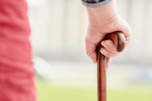 older person with walking stick